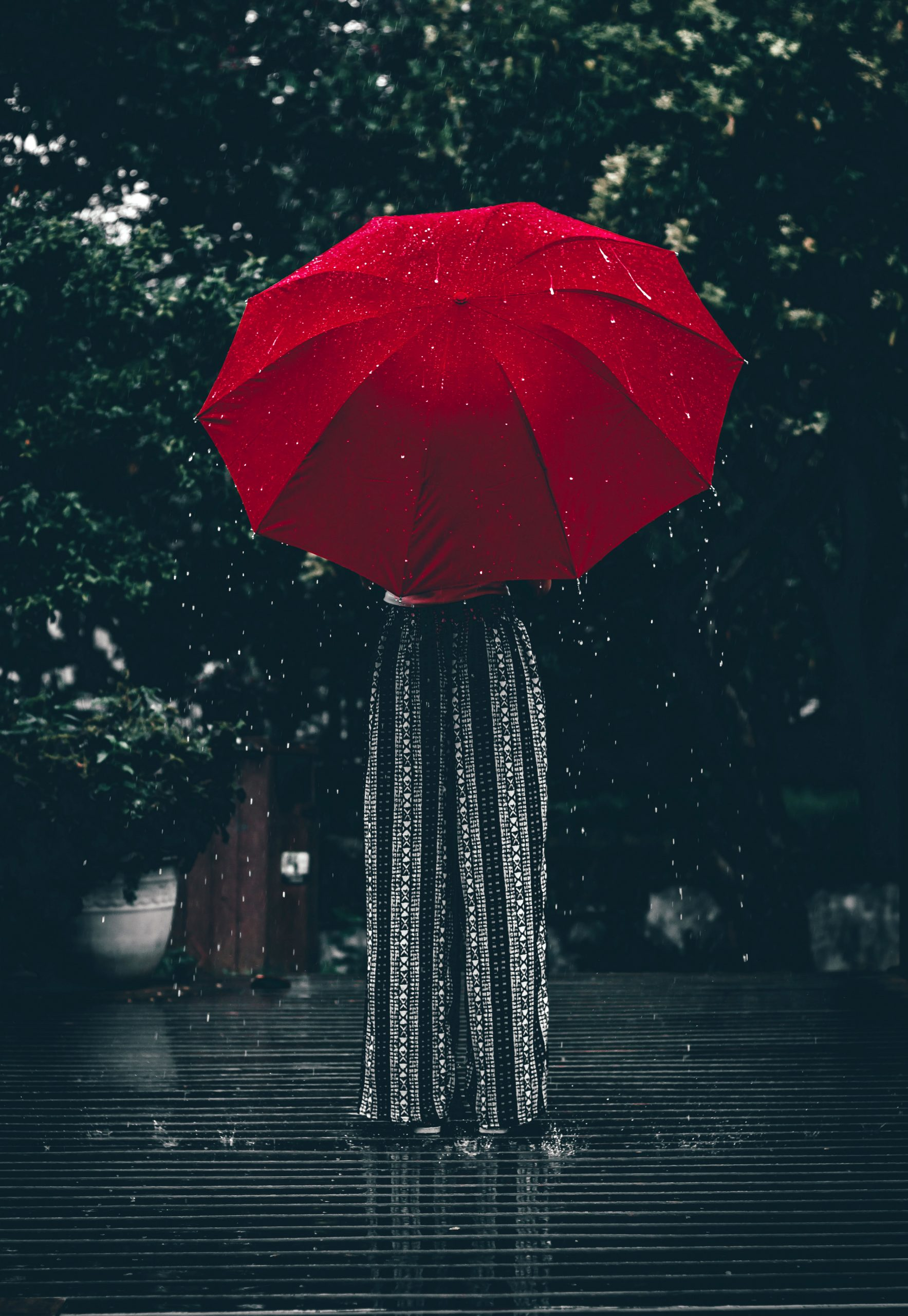 A woman holding a red umbrella.