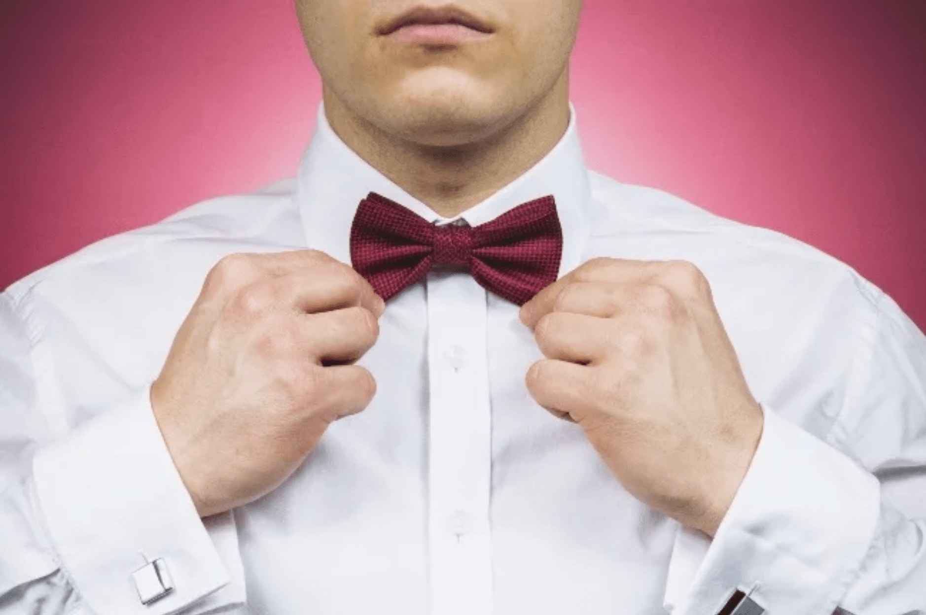 A man straightening his bow tie.